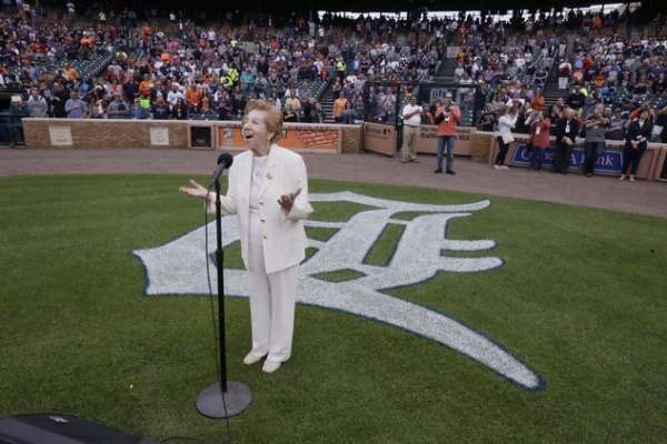 Hermina Hirsch, 89, a Holocaust survivor, sings the national anthem before the baseball game between the Detroit Tigers and the Tampa Bay Rays, Saturday, May 21, 2016, in Detroit. Hirsch's bucket list included singing the anthem before a Tigers game. (AP Photo/Carlos Osorio)