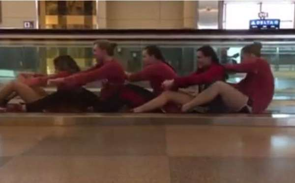 female-swim-team-entertain-themselves-in-airport