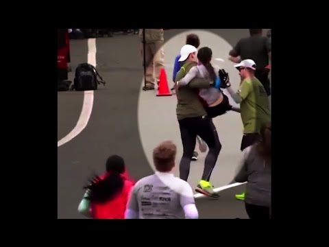 runners help carry fatigued runner across finish line